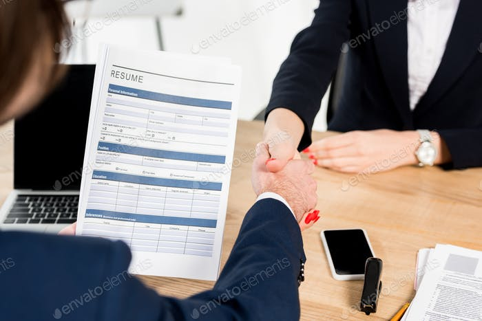 cropped view of recruiter and employee shaking hands in office
