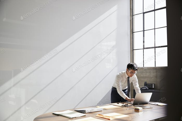 Businessman working alone using laptop in bare office