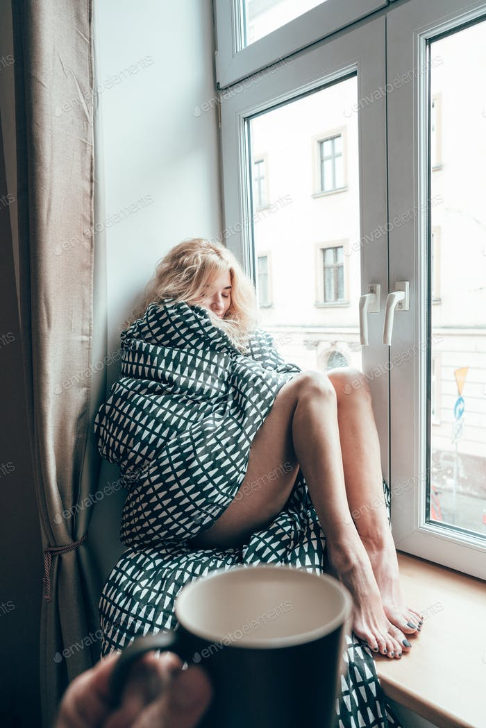 girl sitting on a window in a blanket