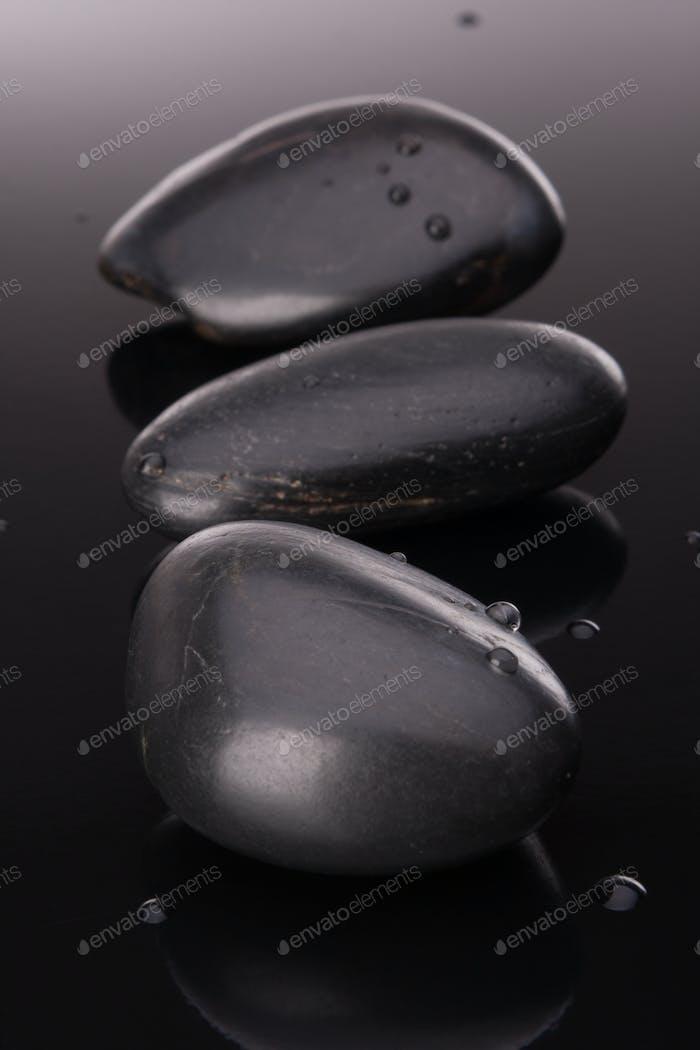 Arreglo de piedra de spa en superficie negra. Concepto sanitario.
