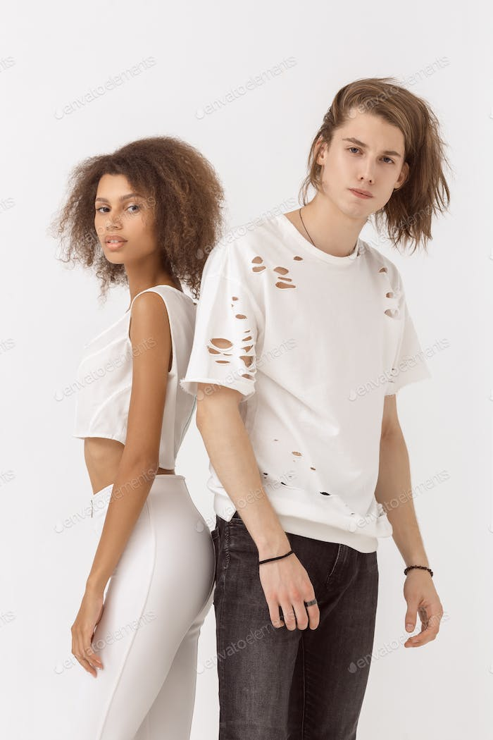 Fashion girl and guy in outlet clothes posing in studio