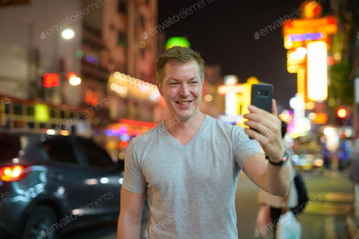Young happy tourist man taking selfie in the busy street of Chinatown at night