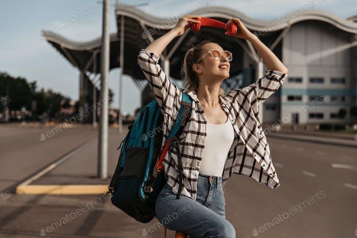 Attraktive Frau in kariertem Hemd und Jeanshose trägt kariertes Hemd, weißes Oberteil und Jeans. Blondes Mädchen