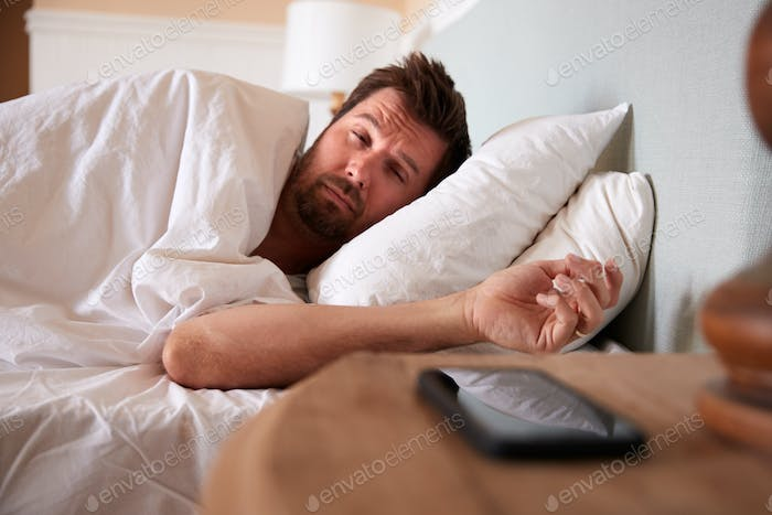 Mid adult man asleep in bed, looking at the smartphone on the bedside table in the foreground