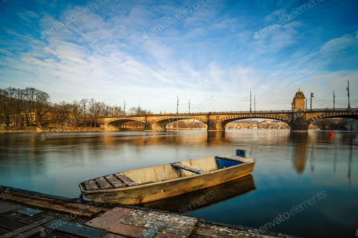 Sunrise view at Vltava river bridge and boat with clear water reflection. Prague Czech republic.