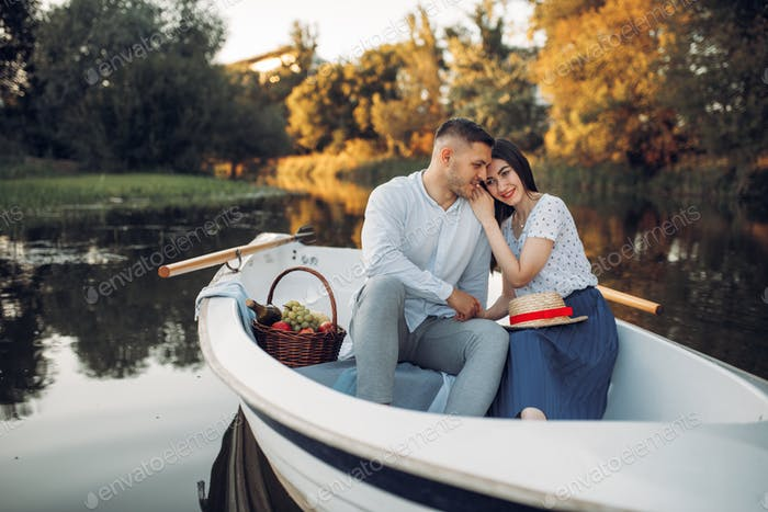 Love couple with fruit basket, relaxing in boat