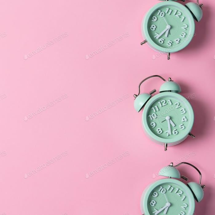 Kreatives Layout von grünen Wecker auf pastellrosa Hintergrund. Minimales Konzept.