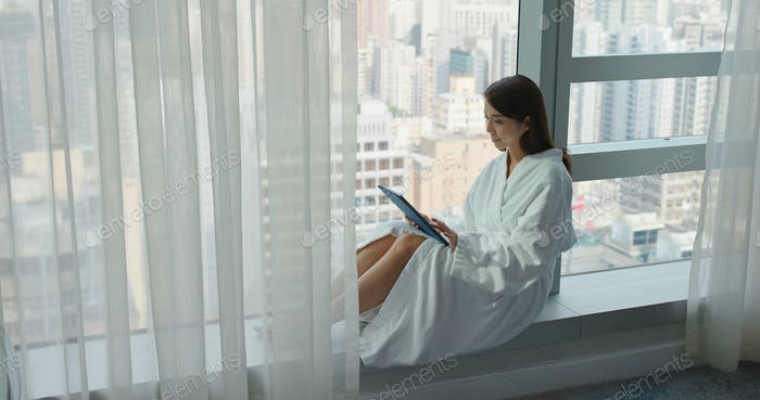 Woman use tablet computer and sit beside window