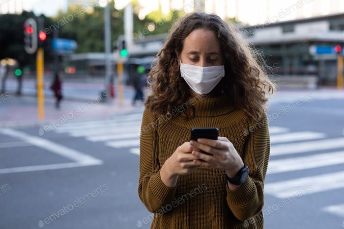 Caucasian woman wearing a protective mask and using her phone in the streets