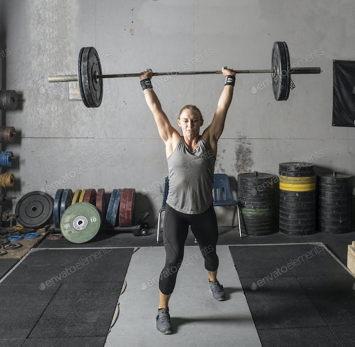 Strong young woman lifting heavy barbell over her head in a gym.