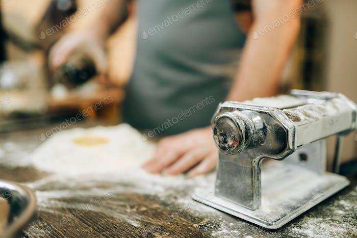 Pasta machine, male chef preparing dough