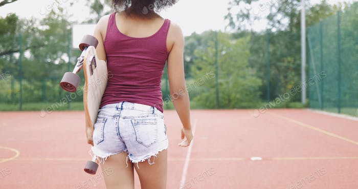 Thumbnail for Girl with skateboard on sports ground