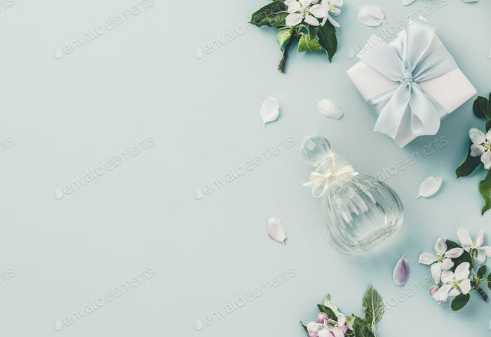 Beautiful perfume bottles and spring flowers on blue background