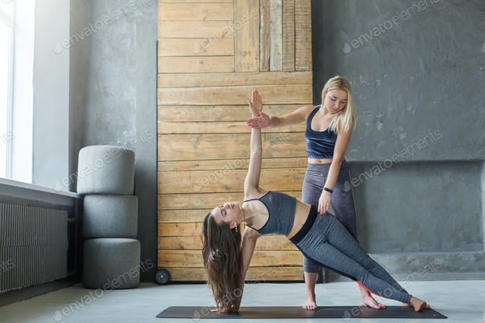 Woman in side plank pose with trainer at yoga class