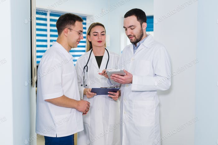 Doctors working in hospital and discussing over medical reports. Medical staff analyzing and working