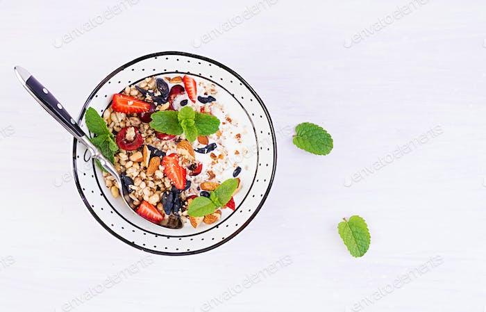Healthy breakfast - granola, strawberries, cherry, honeysuckle berry, nuts and yogurt