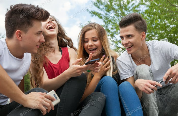 Group of friends sitting together using their phones