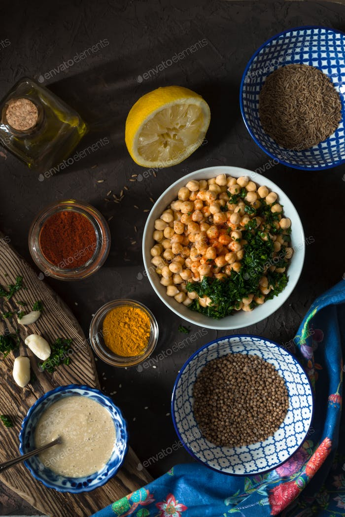 Ingredients for cooking falafel, chickpeas, tahini and spices top view