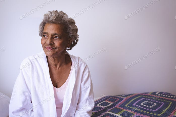 Woman smiling while looking outside the window at retirement home