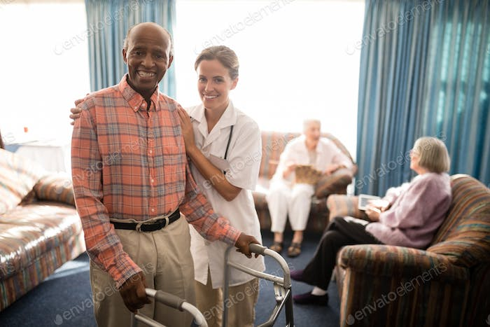 Portrait of smiling female doctor standing by senior man with walker against window