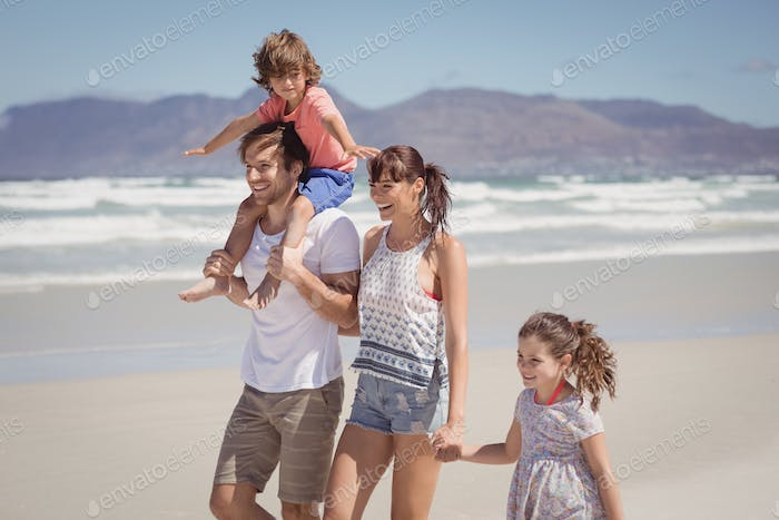 Happy family walking at beach