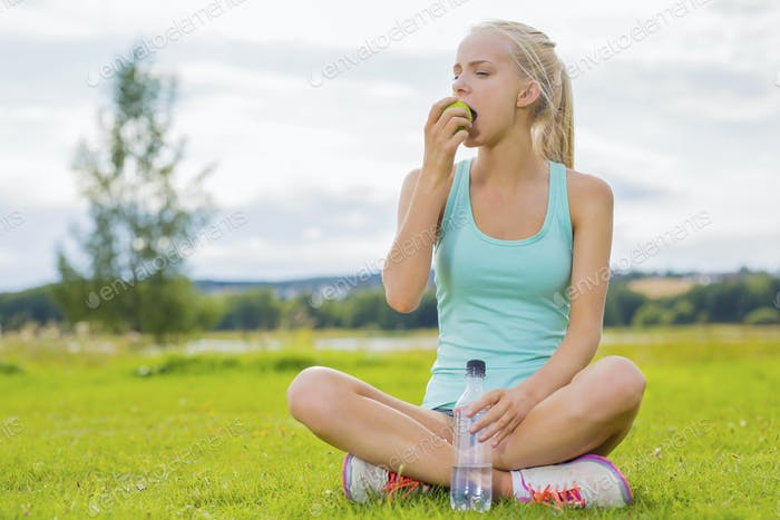 Woman sitting at the grass and eating apple after workout