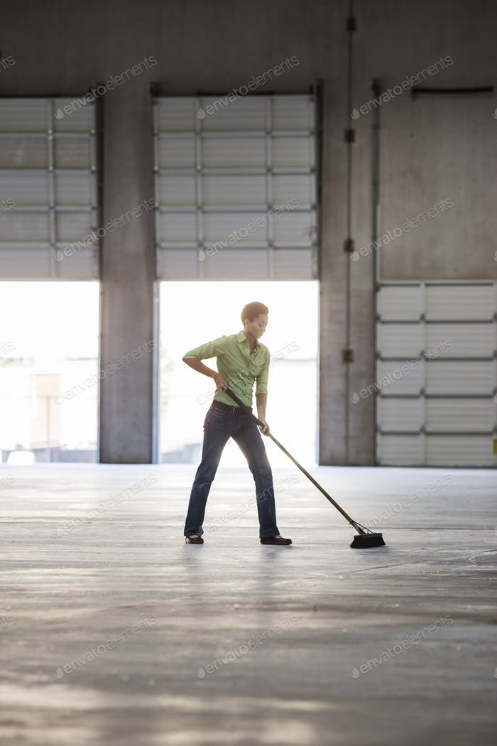 Black woman sweeping up in an empty warehouse space.