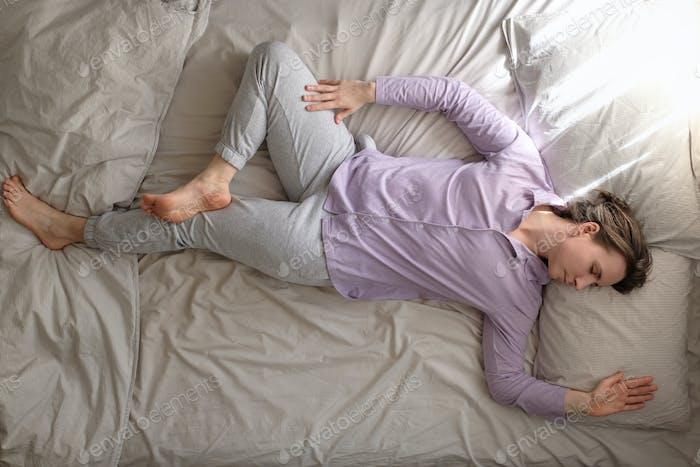 Junge kaukasische Frau, die zu Hause am Bett zu tun Spinal Twist