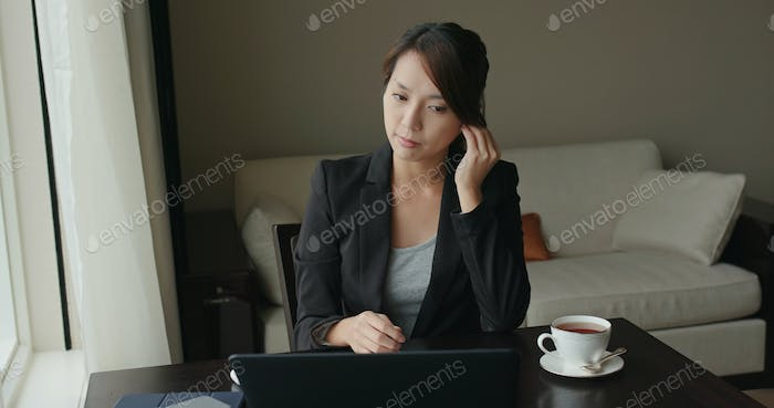 Woman wear earphone to chat online with other colleague on laptop computer at room