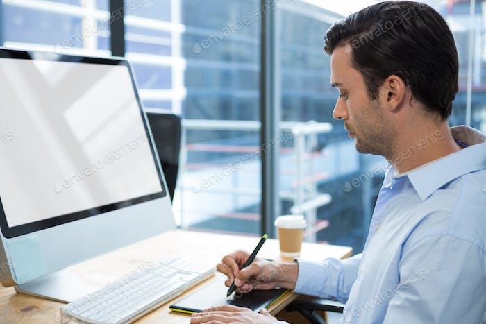 Diseñador gráfico masculino Uso tableta Gráficos en el escritorio