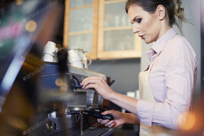 Female barista preparing coffee in cafe