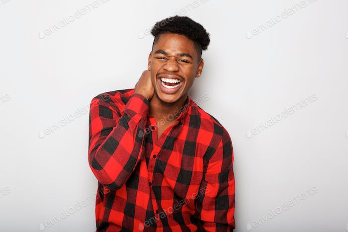 cheerful young African american man laughing against gray background