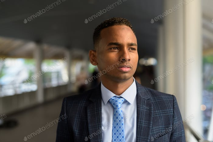 Face of young handsome African businessman in suit thinking at footbridge in the city