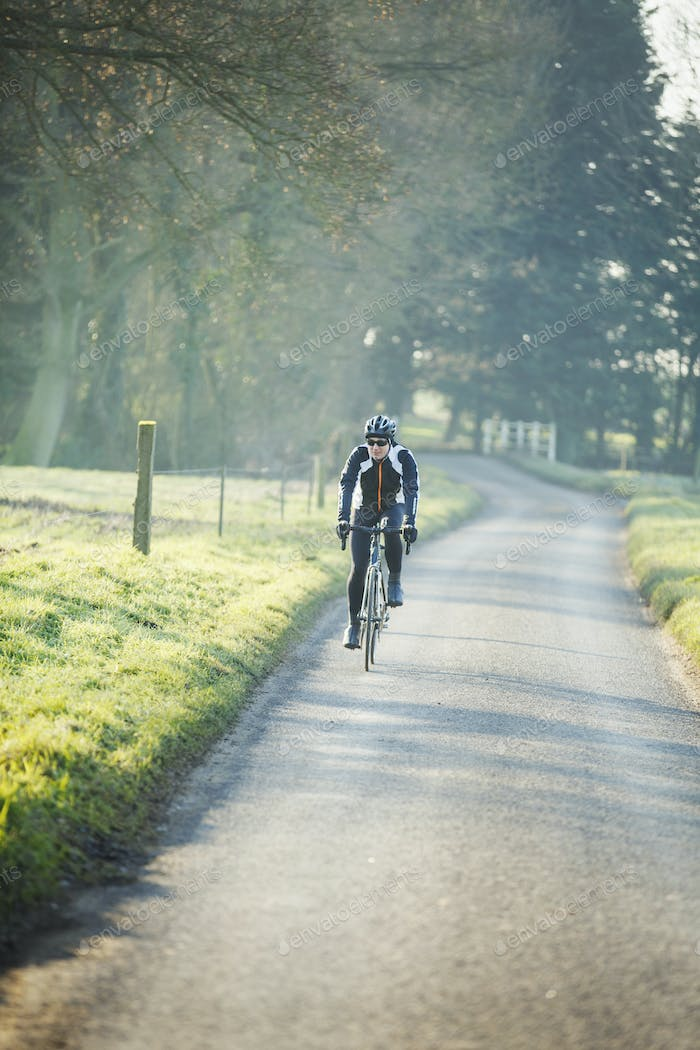 A cyclist pedalling along a country road, rear view.