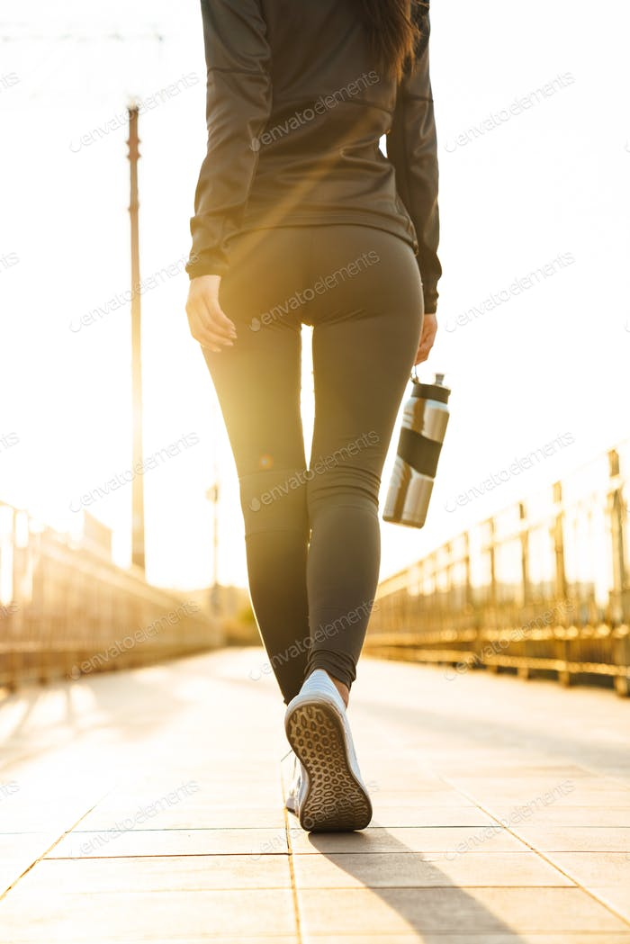 Sports fitness woman walking outdoors.