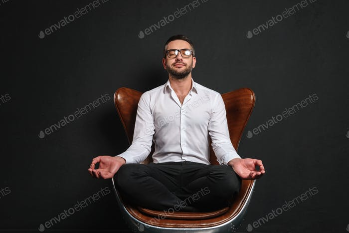 Concentrated businessman meditate.