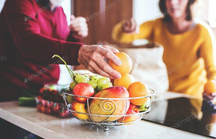 Senior couple unpacking fruit in the kitchen.