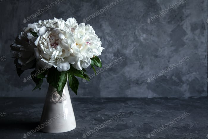 Beautiful peonies on grey concrete background. Wedding, birthday, gift or women's day concept