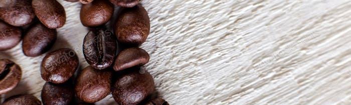 Banner von Kaffeebohnen oder Maserung auf weißem Holzhintergrund.