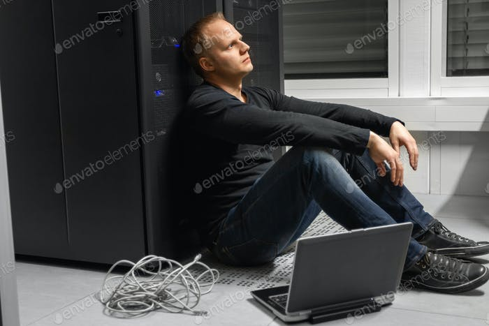 Exhausted Mid Adult Male IT Engineer Against SAN At Datacenter