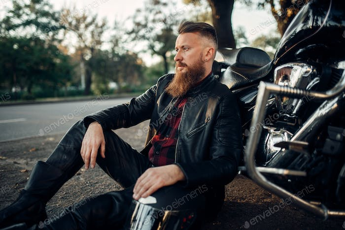 Biker relax after road travel on his chopper