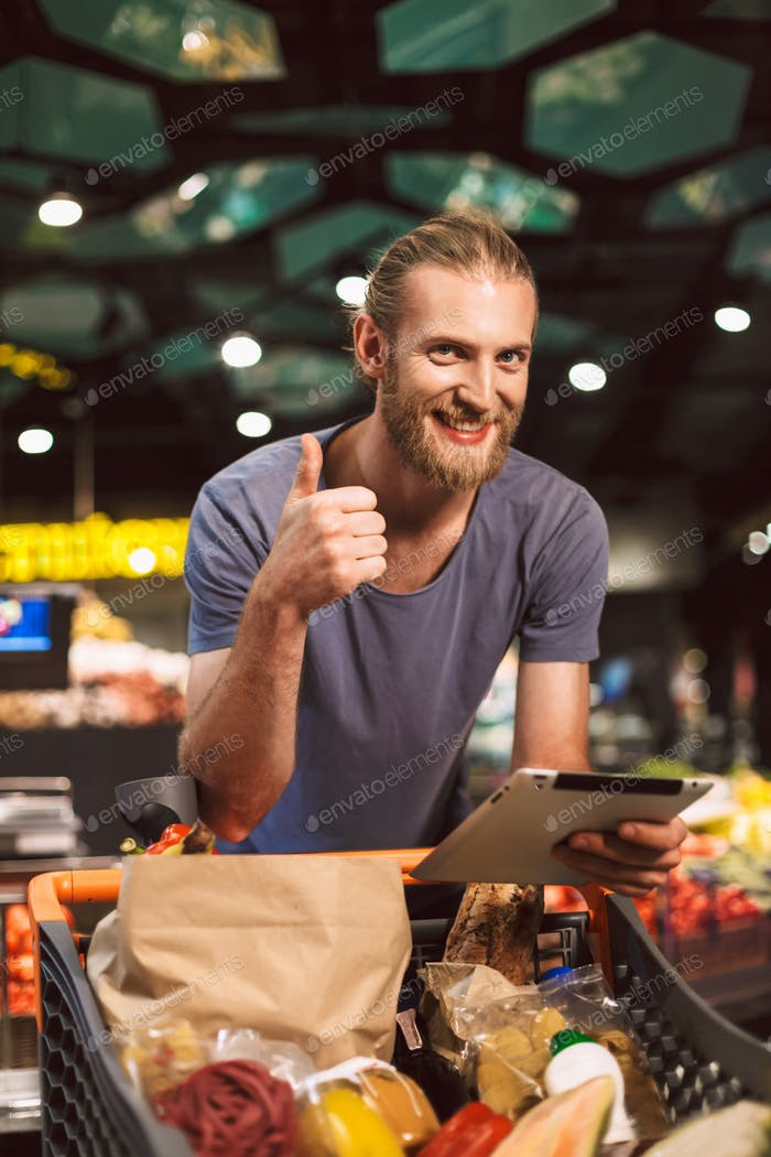 Молодой улыбающийся парень с тележкой полный еды радостно глядя в