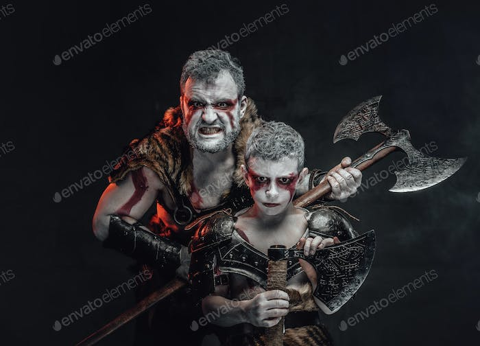 Agressive barbaric warrior with his son in dark background