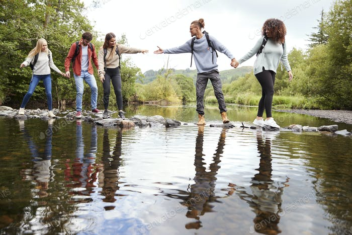 Young adult friends reaching to help each other cross a stream balancing on stones during a hike