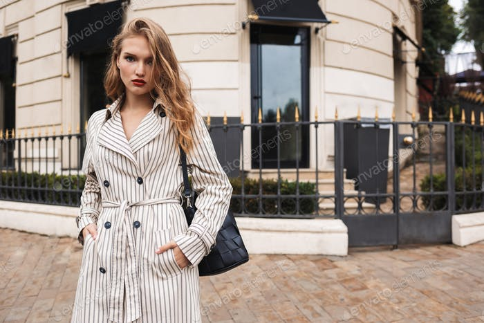 Beautiful pensive girl in striped trench coat with black handbag