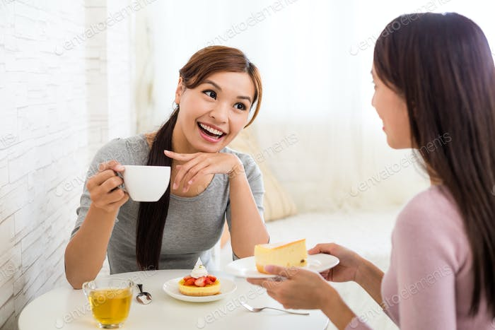 Two woman talk to each other and having cake in shop