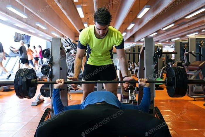 Zwei hübsche junge Männer machen Muskeltraining im Fitnessstudio.