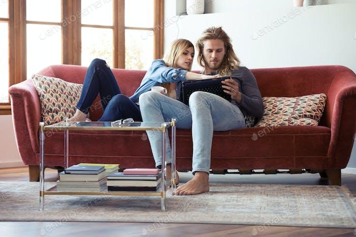Schönes junges Paar Zeichnung mit ihnen digitalen Tablet, während auf dem Sofa zu Hause sitzen.