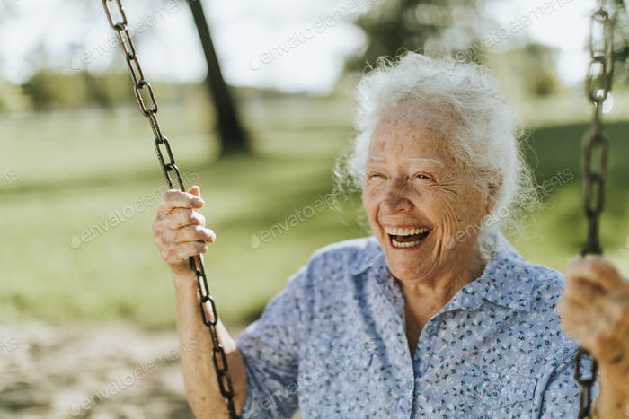 Cheerful senior woman on a swing at a playground