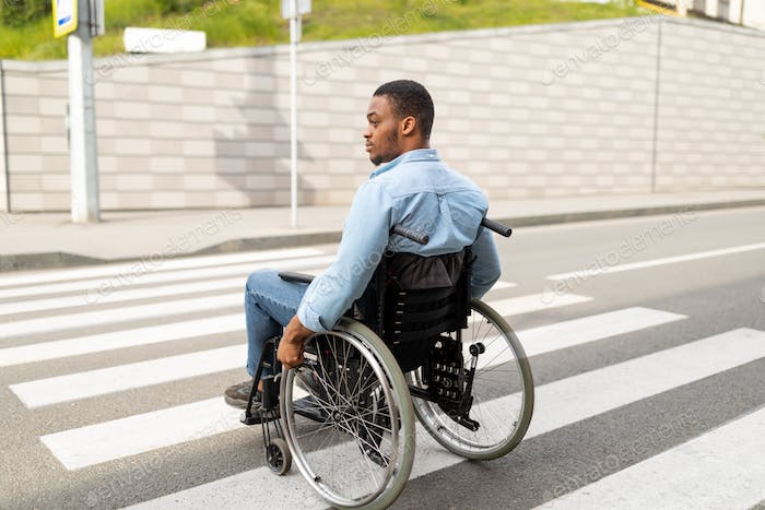 Young disabled black man in wheelchair using crosswalk outdoors. Quality of life and impairment